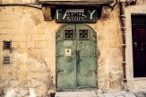 "Green door, stone wall and sign reading ""Family Store"""