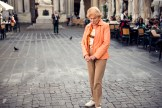 Old woman standing pensively in the street