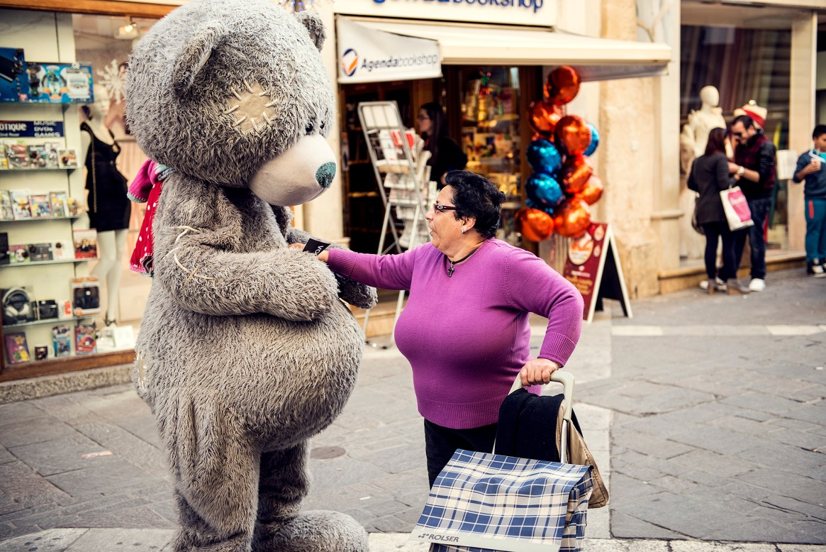 Woman in purple jokes with a person dressed as a giant teddy bear