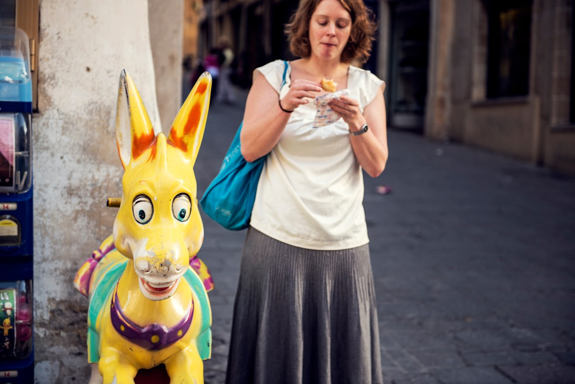 A woman eats her ice cream standing next to a plastic yellow donkey