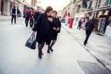 Two women dressed in black walking down the street