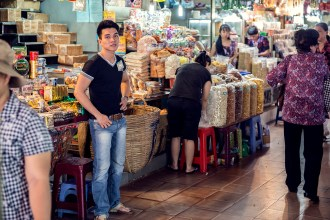 Young man in t-shirt and jeans attending his stall at Ben Thanh market in Ho Chi Minh City
