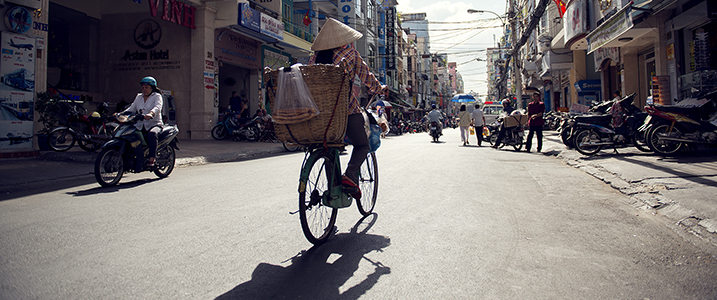 Woman in traditional Vietnamese outfit riding her bicycle in Ho Chi Minh City