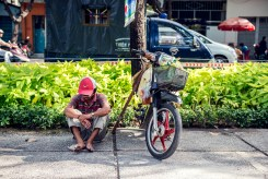 Man resting on the pavement beside his motorbike in Ho Chi Minh City