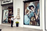 A man poses in apparent unison with two giant fashion posters