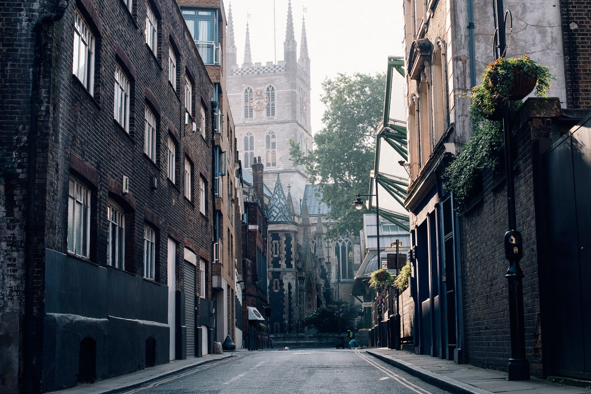 Low key shot of side street with warehouses and Southwark Cathedral in the background