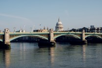 Southwark Bridge, the River Thames and St Paul's Cathedral with clear blue skies at sunrise