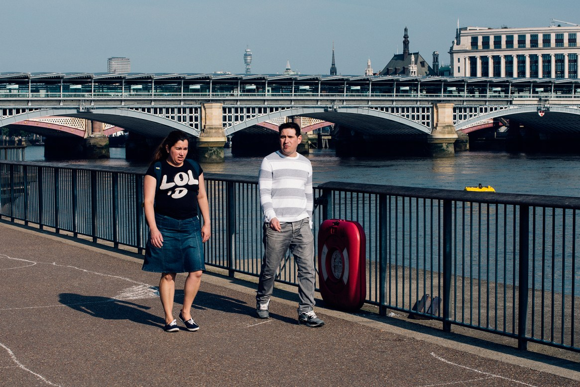 A man in striped shirt and trousers and woman with a black t-shirt reading LOL walk along the River Thames in London at sunrise
