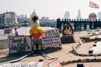 Wide shot of a Bart Simpson figure with Ron, aka the Beach Captain sculpting a rowboat out of sand next to the River Thames in London