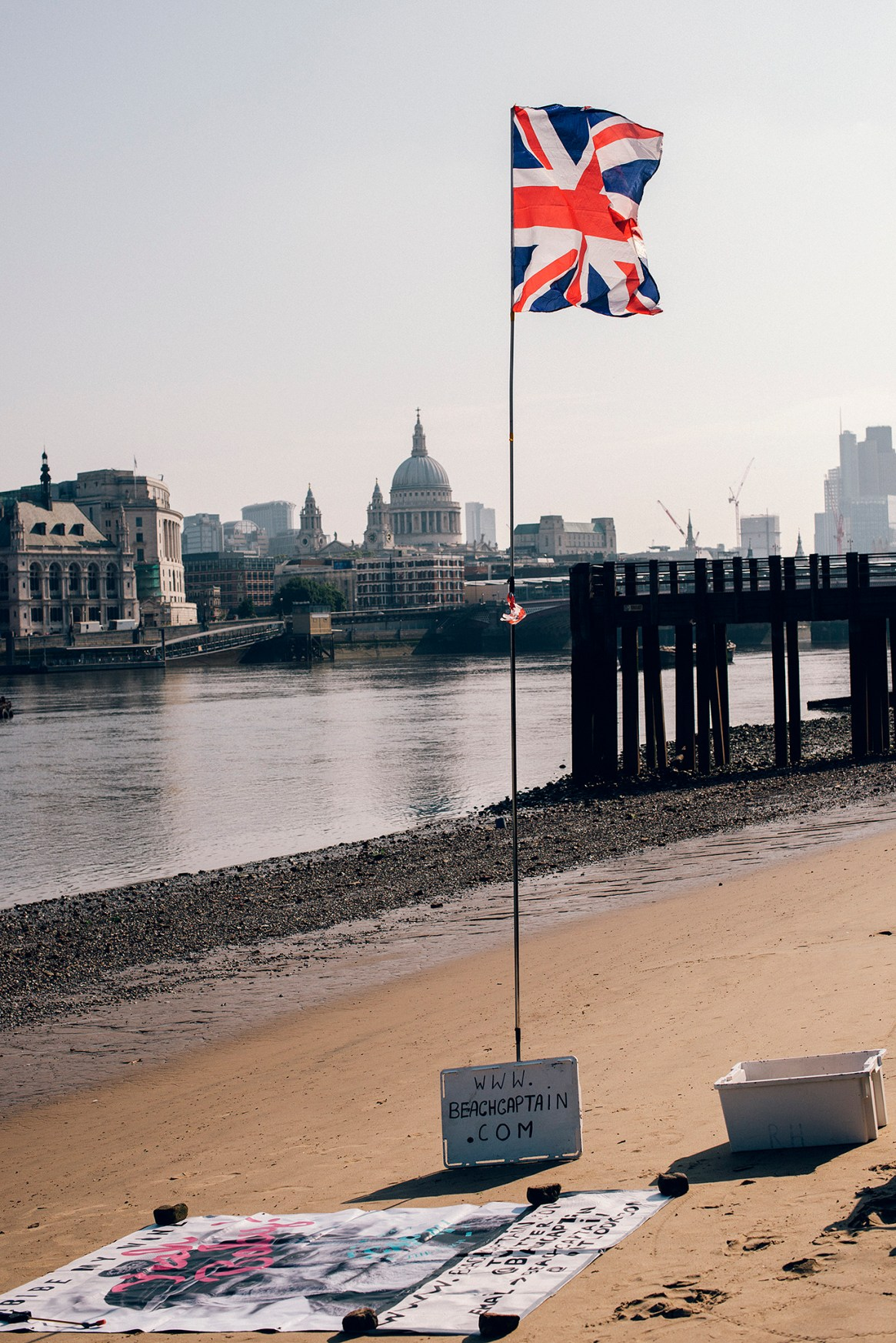 Union Jack waves from a pole planted in the sand next to the River Thames, with St Paul's Cathedral and the City of London in the background at sunrise