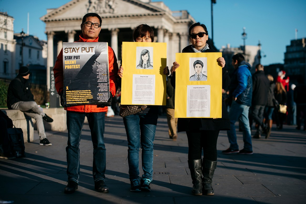 Three people hold up posters in silent protest on Trafalgar Square, London against the South Korean government's reaction to a recent ferry disaster in which a large number of young people died.