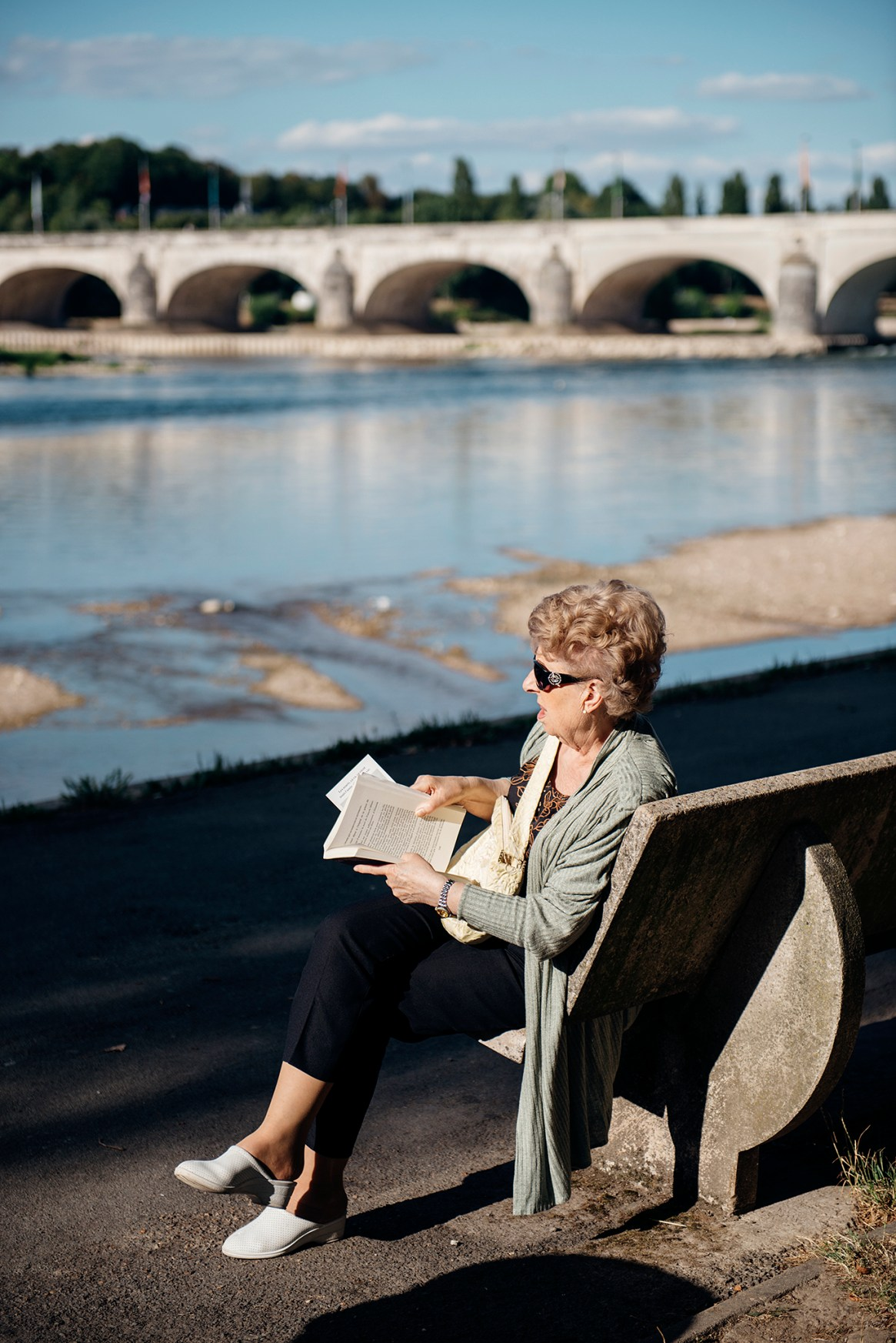 A woman relaxes on a bench on the banks of the Loire River, reading her book in the late afternoon in Tours, France