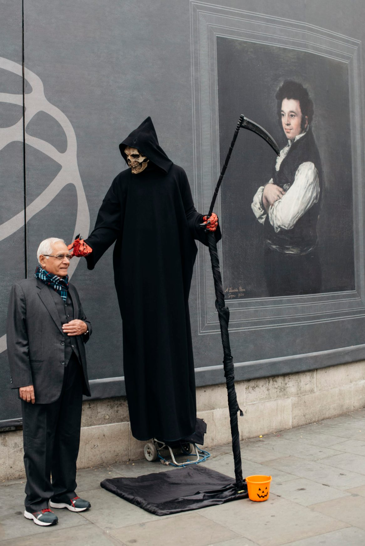 A Trafalgar Square entertainer dressed as the Grim Reaper touches a man's face as they pose in front of a wall with a poster advertising a Goya exhibition outside the National Gallery on Trafalgar Square, London