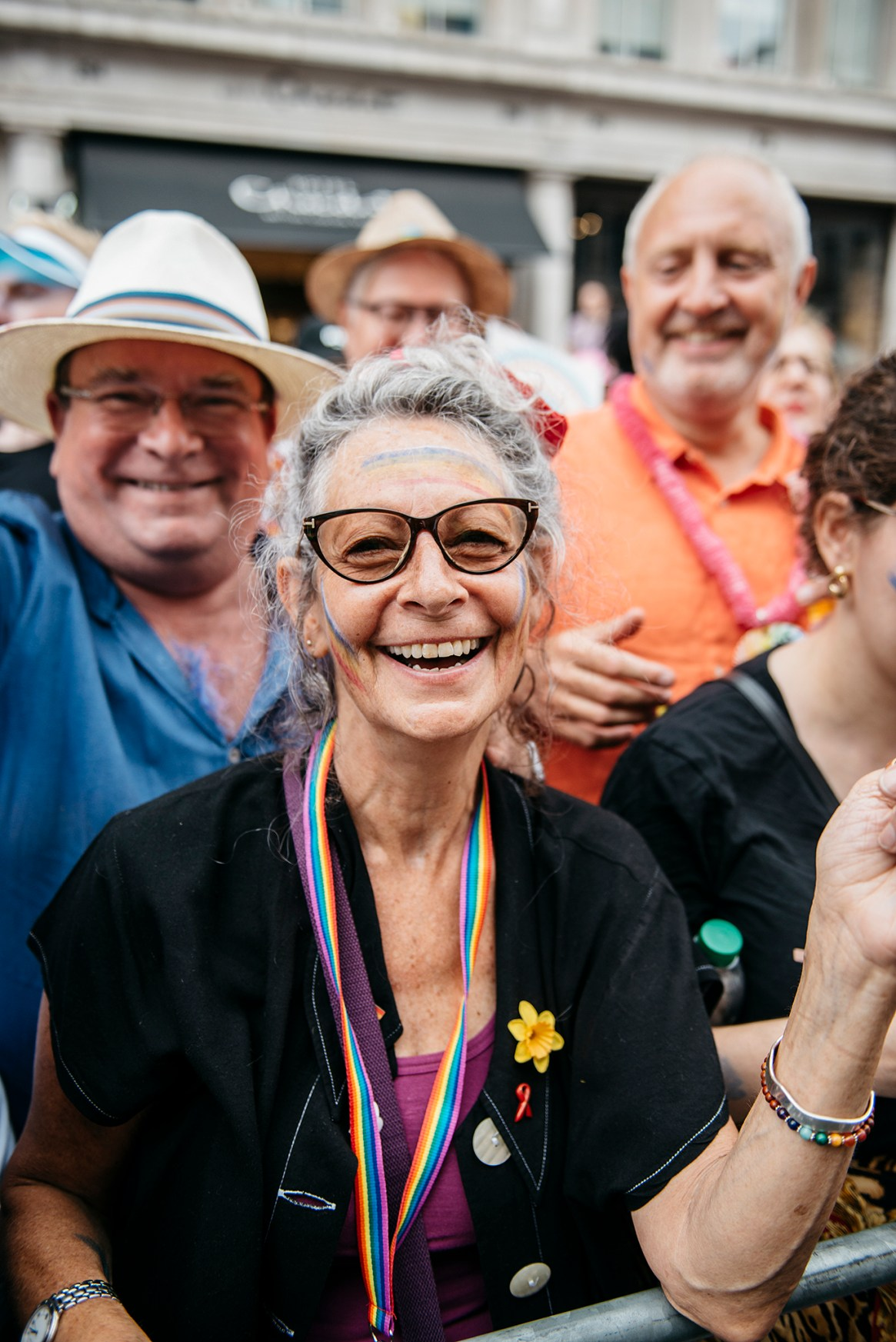 A woman smiles and poses with her friends as they watch the passing Pride in London parade, 2019