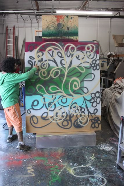 Aaron R. Thomas painting spraypaint on canvas