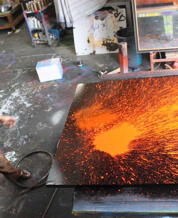 Aaron R. Thomas throwing polyurethane paint on canvas
