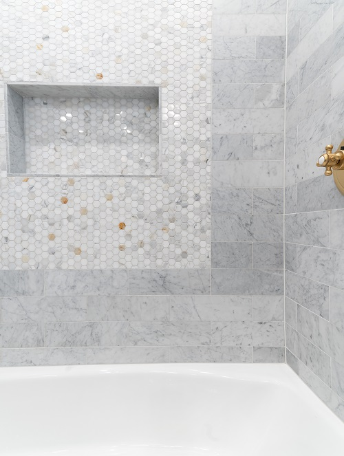 Small white and gold hexagon and rectangle tile above white tub