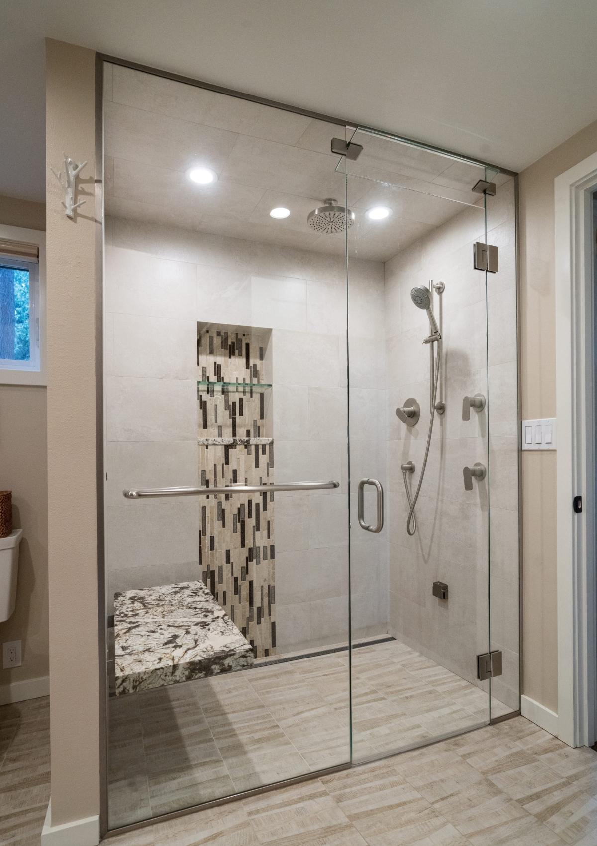 glass shower enclosure with marble bench