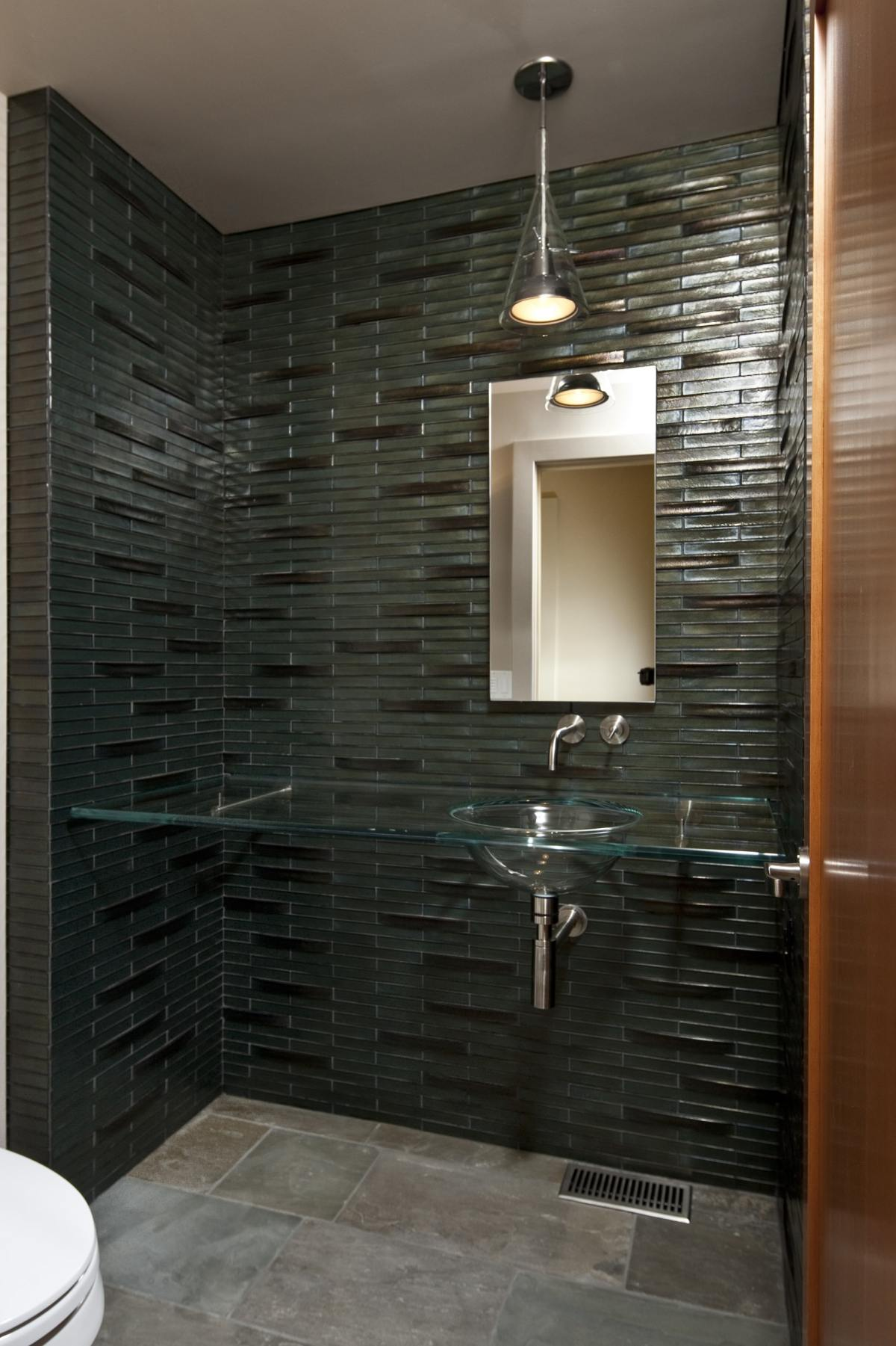 Dark green tile vanity wall with clear glass counter & sink
