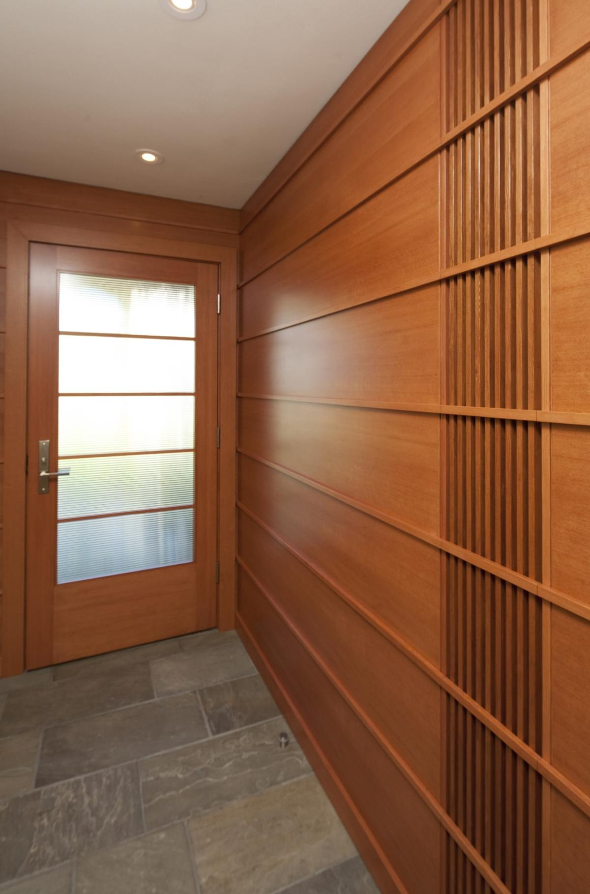 Horizontal and vertical wood detail on hallway wall leading to a frosted glass door