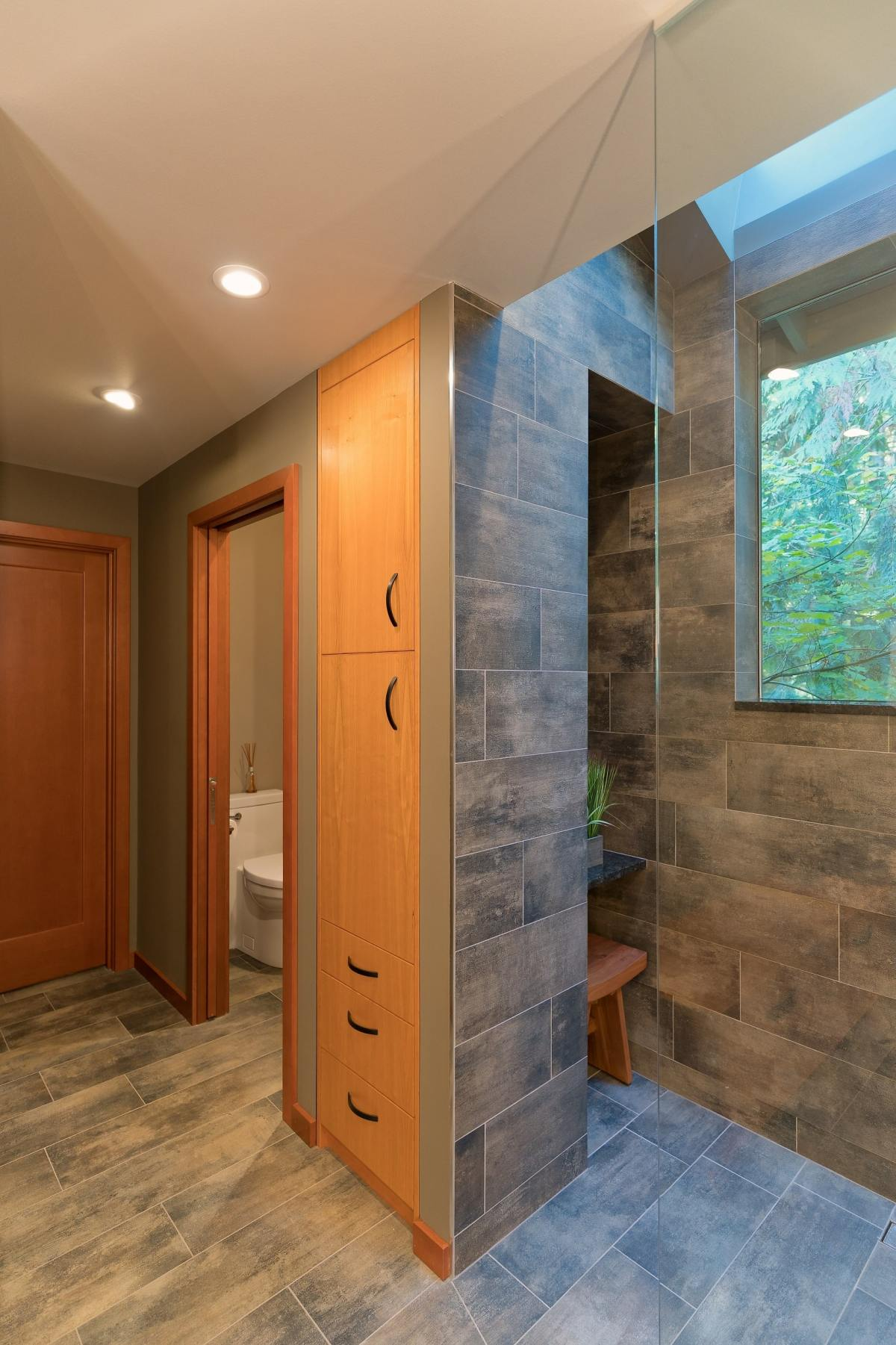 tall tan wood cabinet inbetween a toilet room & shower with glass barrier