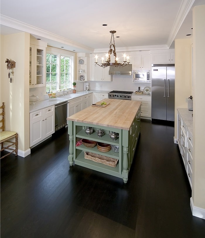 green kitchen island with wood butcher block top in the middle of a white kitchen