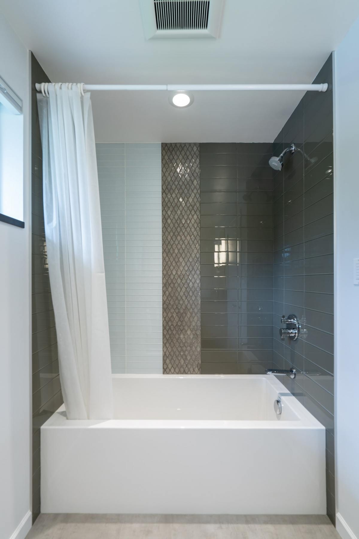 white rectangle tile on left, light grey diamond tile in a middle strip and dark grey rectangle tile on the right above a white bath tub ;