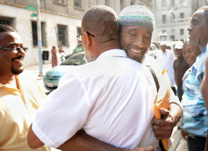 Baltimore, Md--7/25/13--Left, Alexander Mustafa embraces (facing camera) Saleem El-Amin outside Courthouse East after El-Amin and several inmates convicted of murder are released. Mustafa, who had been in prison, but has been out for 17 years, met El-Amin while they were incarcerated.  The men just released were convicted before 1980 and the Court of Appeals ruled jurors had been given improper instructions.  Kim Hairston/The Baltimore Sun--#1841