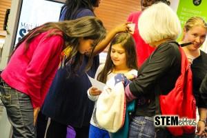 Kriti helping a little Stemette fill out her networking sheet