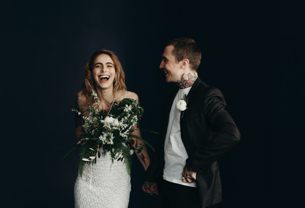 London Wedding Photography by Stephanie Green. A wild bride smiles holding a bouquet, whilst her tattooed husband laughs in admiration