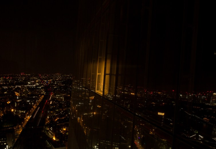 The Shard at night by Stephanie Green Photography. An ambient light exits a window, and reflections of the city lights are all around it