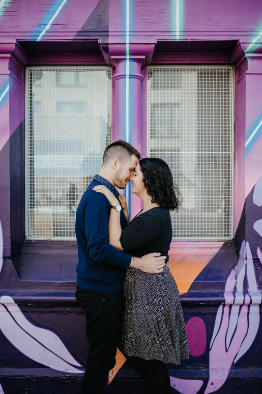 A picture of a loving couple in front of a colourful wall