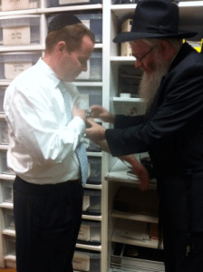 Rabbi Mentz placing Jonathan's first piece of Tefillin on him