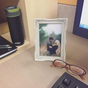 couple engagement photos rustic ornate frame desk work job contigo mug glasses notebook windows