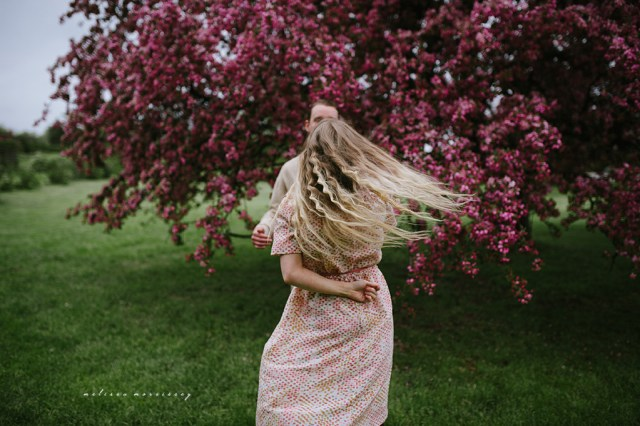 stephanie de montigny pink cherry blossoms photos ottawa melissa morrissey photography engagement photos, bride, blue eyes, curly blonde hair, stunning pink polka dot vintage dress, groom smiling natural cardigan leather elbow patches, dancing