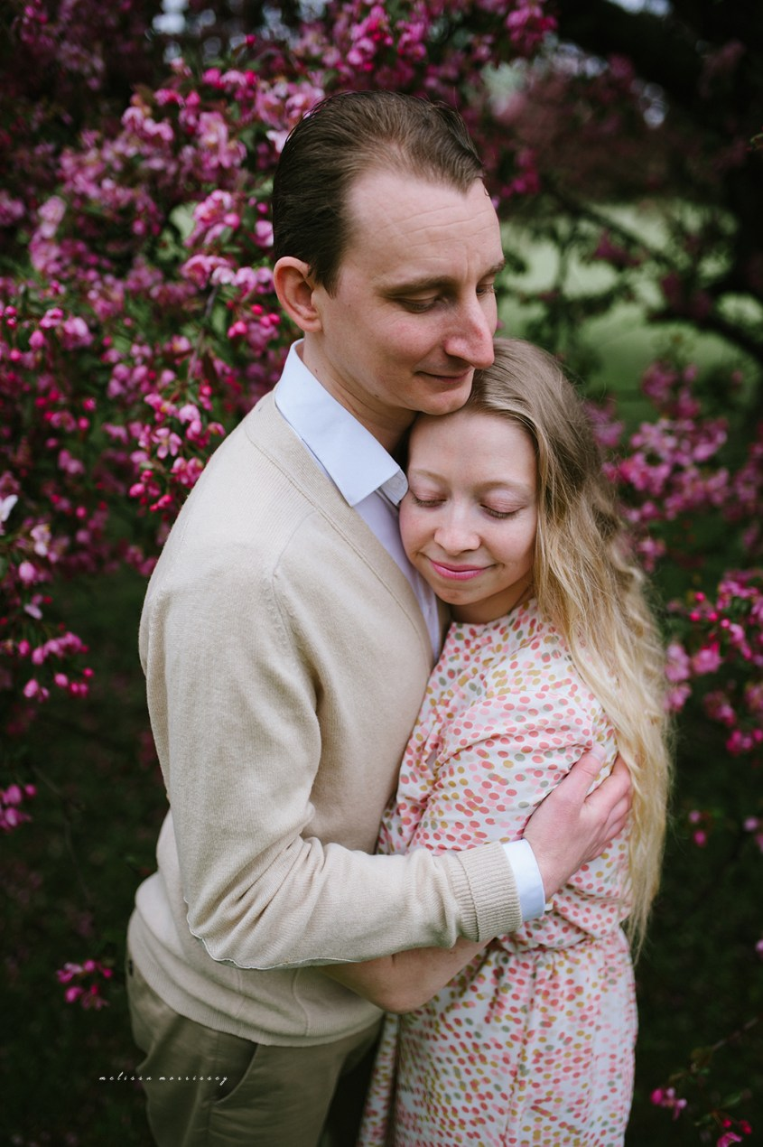 stephanie de montigny pink cherry blossoms photos ottawa melissa morrissey photography engagement photos, bride, blue eyes, curly blonde hair, stunning pink polka dot vintage dress, groom smiling natural cardigan leather elbow patches, hugging lovingly