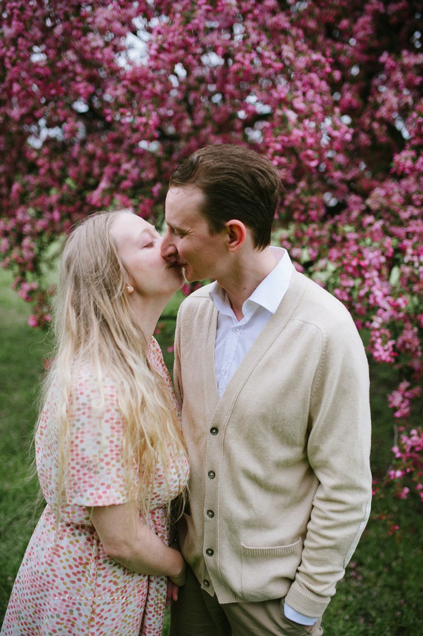 stephanie de montigny pink cherry blossoms photos ottawa melissa morrissey photography engagement photos, bride, blue eyes, curly blonde hair, stunning pink polka dot vintage dress, groom smiling natural cardigan leather elbow patches, kissing