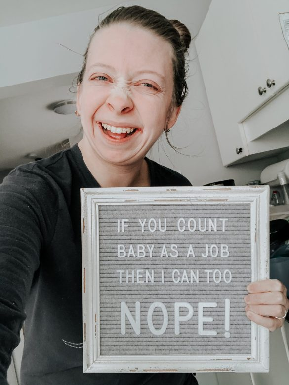 mama holding up letterboard quote raising a baby is a full time job for a work from home parent