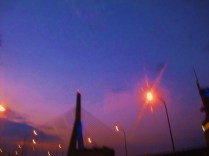 A blurred flash of freshly-fallen night behind the Zakim Bridge