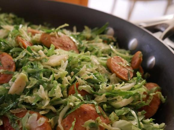 Sauteed brussels sprouts shreds with slices of chicken sausage in a frying pan