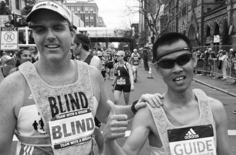 Visually impaired runner Erich Manser ran the Boston Marathon with a guide and with the assistance of Aira technology. Erich is pictured on the left wearing a camera on glasses which captured images and transmitted them to his Aira Explorer for audio description.
