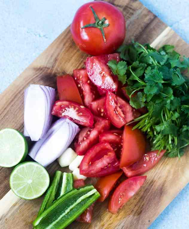 Fresh tomatoes, red onion, jalapeno, cilantro, and lime on a cutting board.