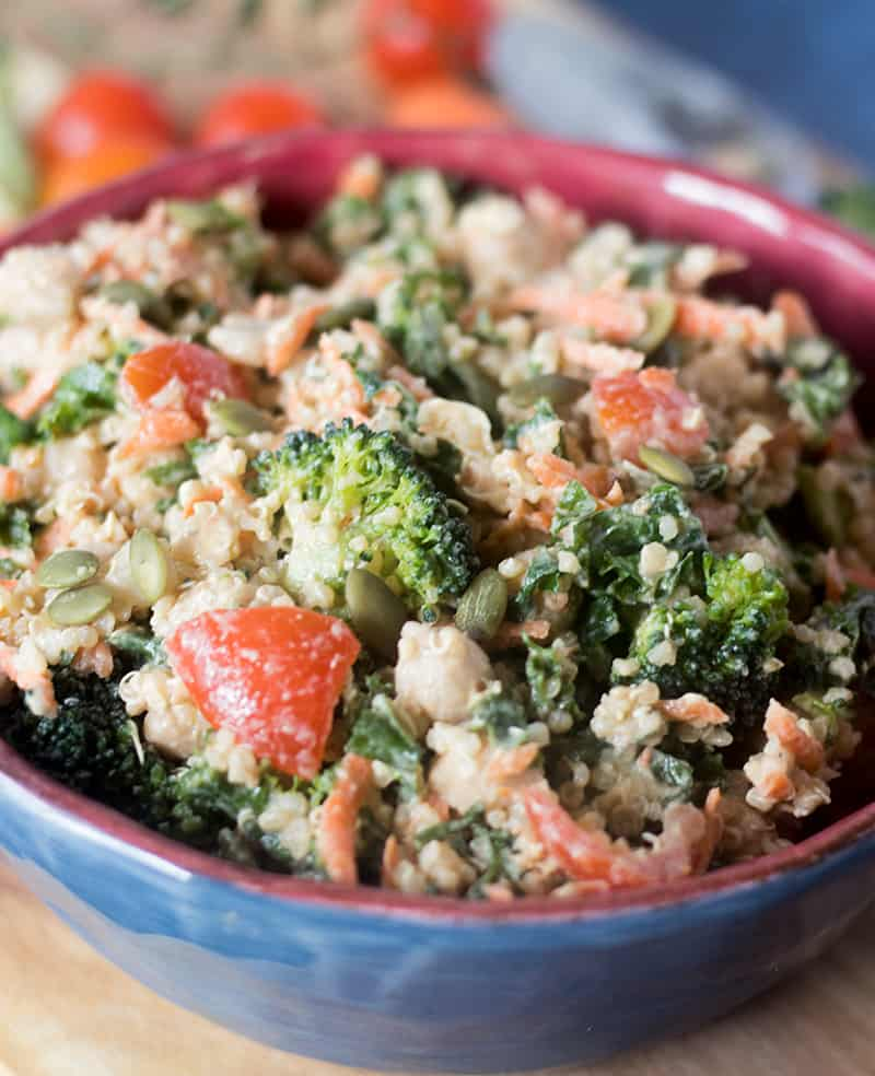 kale, quinoa, broccoli, carrots, grape tomatoes, chickpeas in all bowl tossed with tahini dressing