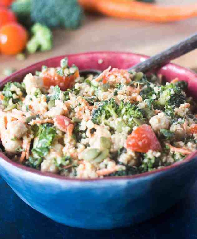 kale, quinoa, broccoli, carrots, chickpeas, cherry tomatoes in a bowl tossed with tahini dressing