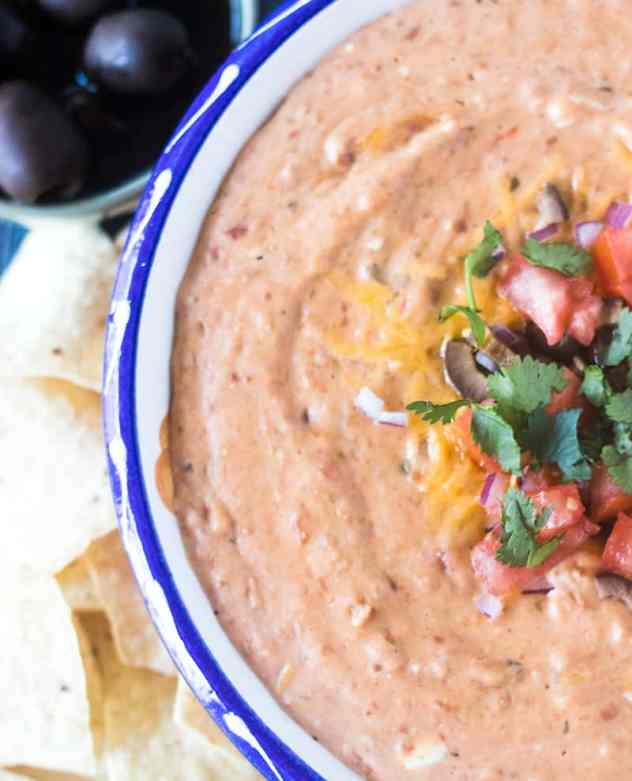 Bean dip in a bowl with chopped tomato, red onion, black olives and cilantro with tortilla chips beside it.