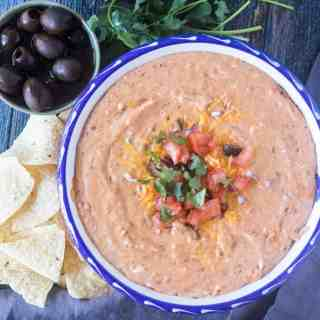Bean dip in a bowl with chopped tomato, red onion, black olives, cilantro with a bowl of black olives and tortilla chips beside it.