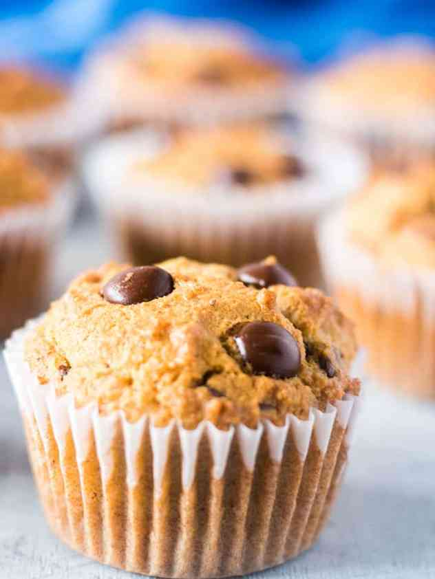 Coconut Flour Chocolate Chip Muffins in white baking cup with blue towel in background.