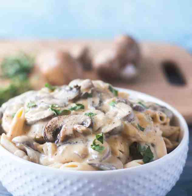 Mushroom Stroganoff topped on penne pasta served in a white bowl.