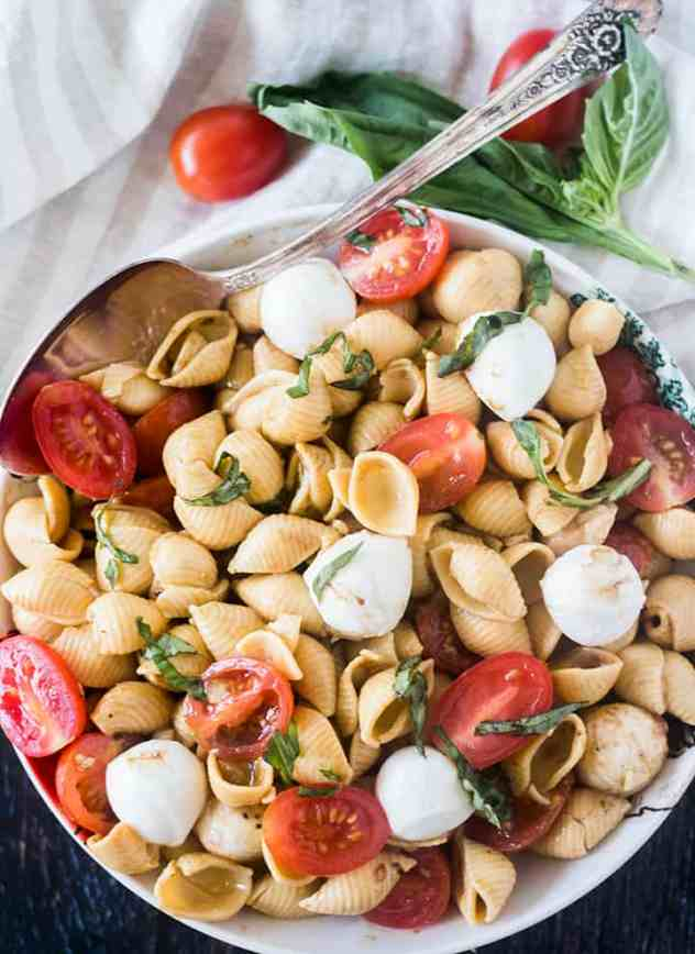 Caprese Pasta Salad in a bowl with a spoon and tomatoes and fresh basil in background.