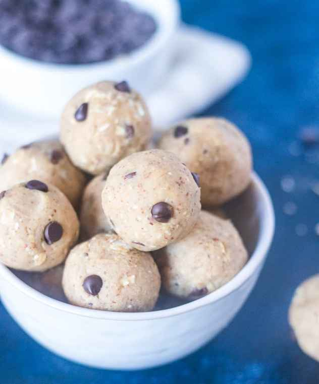 Chickpea Cookie Dough Bites in a white bowl with a bowl of chocolate chips in background.